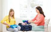 Two smiling teenage girls packing suitcase at home — Stock Photo