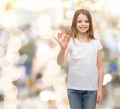 Little girl in white t-shirt showing ok gesture — Stock Photo
