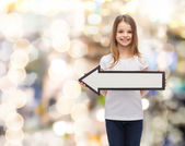 Smiling girl with blank arrow pointing left — Stock Photo