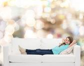 Smiling little girl lying on sofa — Stock Photo