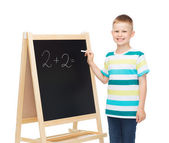 Happy little boy with blackboard and chalk — Stock Photo