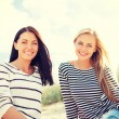 Smiling girlfriends having fun on the beach — Stock Photo #49437273