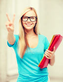 Smiling student with folders showing victory sign — Stock Photo
