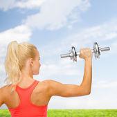 Mujer deportiva con mancuerna de acero pesado de espalda — Foto de Stock