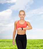 Smiling woman with heart rate monitor on hand — Stock Photo