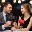 Young couple with glasses of wine at restaurant — Stock Photo #49440435