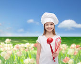 Smiling girl in cook hat with ladle and whisk — Stock Photo