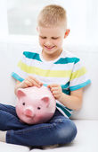 Smiling little boy with piggy bank and money — Stock Photo