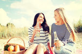 Girlfriends with bottles of beer on the beach — Stock fotografie
