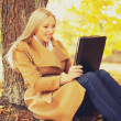 Woman with tablet pc in autumn park — Stock fotografie #49604129