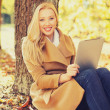 Woman with tablet pc in autumn park — Foto de Stock   #49604155