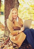 Kvinna med tabletpc i höst park — Stockfoto