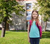 Smiling girl with school bag showing thumbs up — Stock Photo