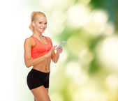 Smiling sporty woman with smartphone and earphones — 图库照片