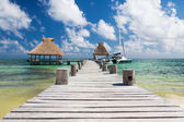 Wooden pier with blue water around — Foto Stock