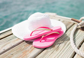Close up of hat and slippers at seaside — Stock Photo