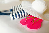 Close-up of beach bag, hat and flip-flops on bed — Stock Photo