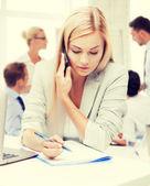 Mulher de negócios com o telefone no escritório — Fotografia Stock