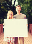 Romantic couple with blank white board — Stock Photo