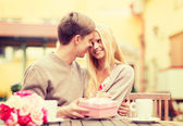 Romantic happy couple with gift in the cafe — Stock Photo