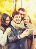 Group of friends taking selfie in autumn park — Stock Photo