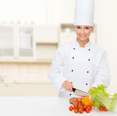 Smiling female chef chopping vegetables — Stock Photo