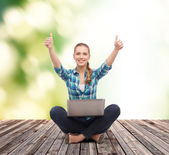 Smiling woman with laptop and showing thumbs up — Stock Photo