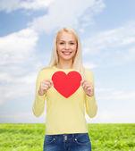 Usmívající se žena s červeným srdcem — Stock fotografie
