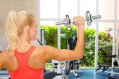 Sportiga kvinnan med tunga stål hantel från baksidan — Stockfoto