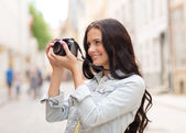 Smiling teenage girl with camera — Stock Photo