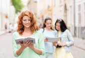 Smiling teenage girls with city guides and camera — Stockfoto