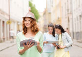 Smiling teenage girls with city guides and camera — Foto Stock