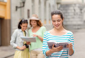 Smiling teenage girls with city guides and camera — Stock Photo