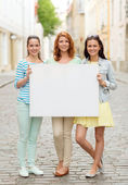 Smiling teenage girls with blank billboard — Stock Photo