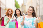 Smiling teenage girls with shopping bags on street — Stock Photo