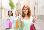 Smiling teenage girls with shopping bags on street — Foto Stock