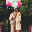 Couple with colorful balloons kissing in the park — Stock Photo #49743259