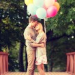 Couple with colorful balloons kissing in the park — Stock Photo #49809395