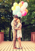 Couple with colorful balloons kissing in the park — Stock Photo