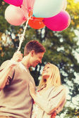 Smiling couple with colorful balloons in park — Stok fotoğraf