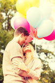 Smiling couple with colorful balloons in park — Stock Photo