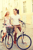 Smiling couple with bicycles in the city — Stok fotoğraf