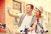 Couple with bicycles taking photo with camera — 图库照片