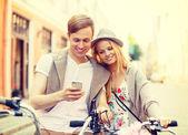 Casal com smartphone e bicicletas na cidade — Foto Stock
