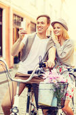 Couple with bicycles and smartphone in the city — Stockfoto