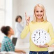 Student with wall clock and finger up — Stock Photo #49814287