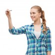 Smiling young woman writing on virtual screen — Stock Photo #49814903