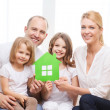 Smiling parents and two little girls at new home — Stock Photo #49814943