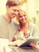Smiling couple with tablet pc computer in cafe — Stock Photo