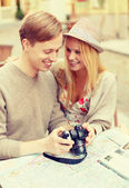 Smiling couple with photo camera — Stock Photo